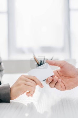 cropped image of patient giving business card to doctor in clinic