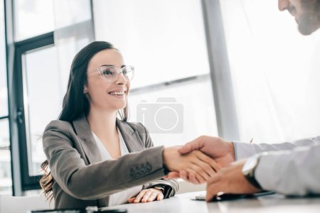 smiling female patient and doctor shaking hands in clinic