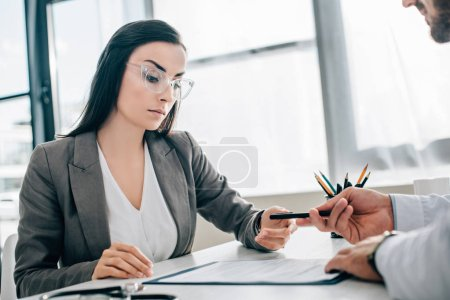 cropped image of doctor giving pen to female patient to sign insurance claim form in clinic