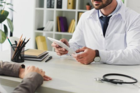 cropped image of doctor holding tablet in clinic