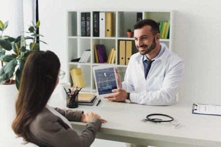 smiling doctor showing tablet with loaded tumblr page to patient in clinic