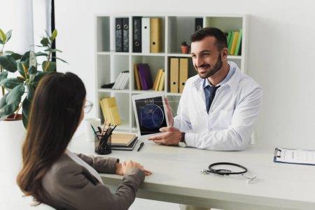 Photo pour Médecin généraliste souriant montrant ipad patient en clinique - image libre de droit