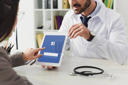 cropped image of doctor showing patient tablet with loaded facebook page in clinic