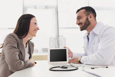 Photo pour Docteur sourire montrant patient tablet avec écran blanc en clinique - image libre de droit