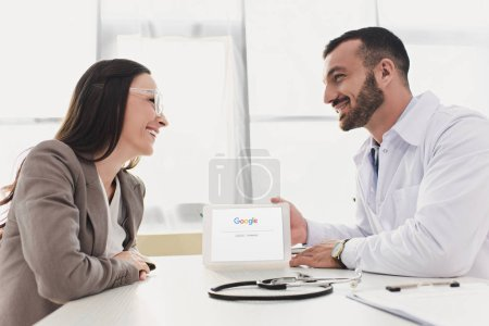 smiling doctor showing patient tablet with loaded google page in clinic