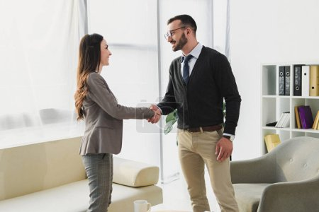 side view of happy patient and psychologist shaking hands in doctors office