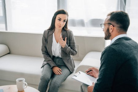 cheerful patient looking at psychologist in doctors office