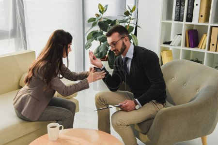 patient showing smartphone to psychologist in doctors office