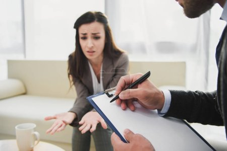 Photo for Cropped image of crying patient talking and psychologist taking notes in doctors office - Royalty Free Image