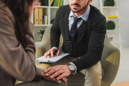 cropped image of psychologist touching hand of patient in doctors office