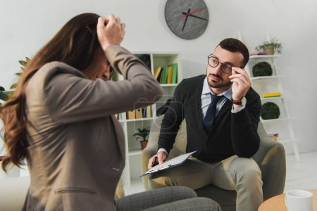 depressed patient touching head in psychologist office