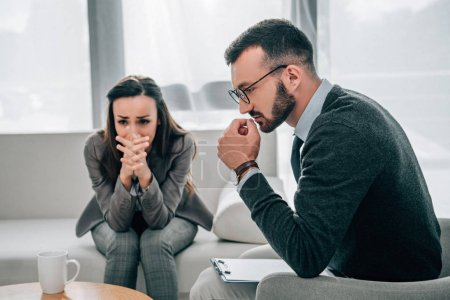 depressed patient crying and pensive psychologist sitting in doctors office