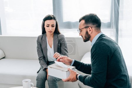 psychologist giving napkins to sad crying patient in doctors office