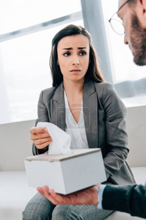 psychologist giving napkins to upset patient in doctors office