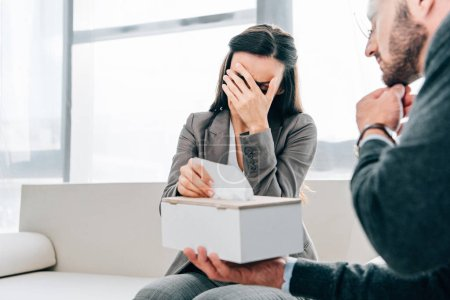 psychologist giving napkins to crying patient in doctors office