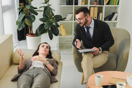 patient lying on sofa and talking with psychiatrist in office
