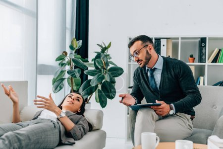 patient lying on sofa and talking to therapist in office