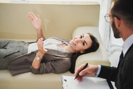 happy patient lying on sofa and talking to psychologist in doctors office