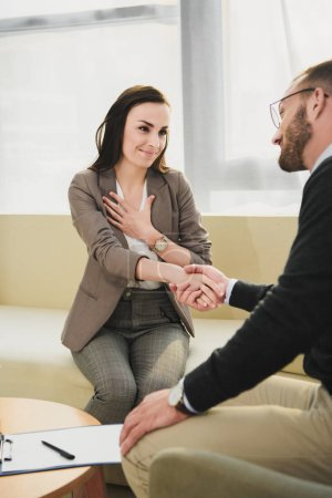 smiling patient and psychologist shaking hands in doctors office