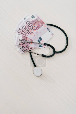 elevated view of stethoscope and euro banknotes on table in clinic, health insurance concept