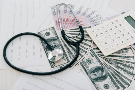 stethoscope, money and calculator on table in clinic, health insurance concept