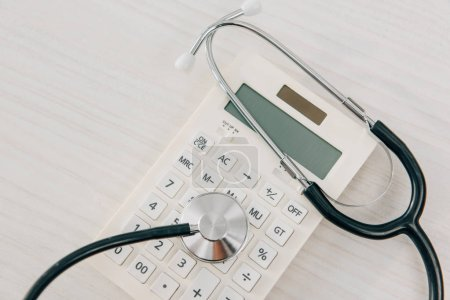 top view of stethoscope lying on white calculator, health insurance concept