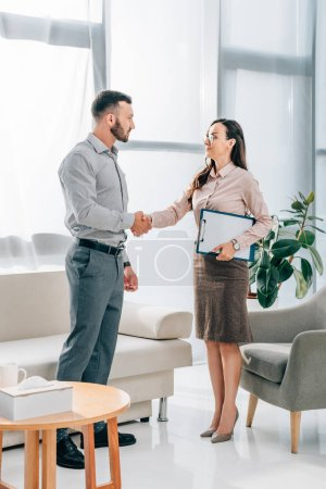 psychologist and patient shaking hands in office