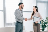 smiling psychologist and patient shaking hands in office