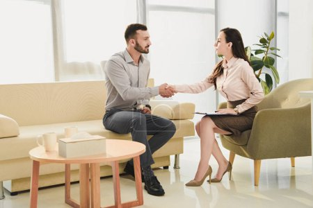 female psychiatrist and patient shaking hands in office