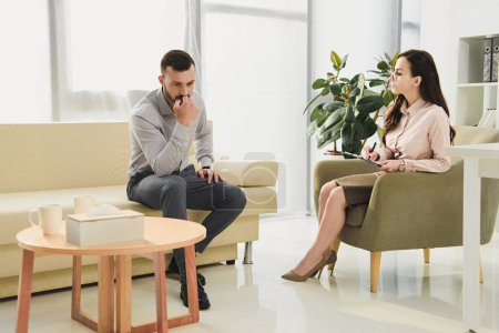 psychiatrist and sad patient having consultation in office