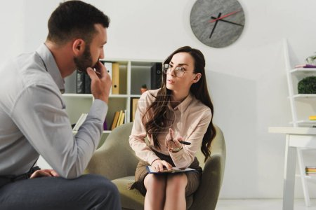 professional psychiatrist and sad patient having consultation in office