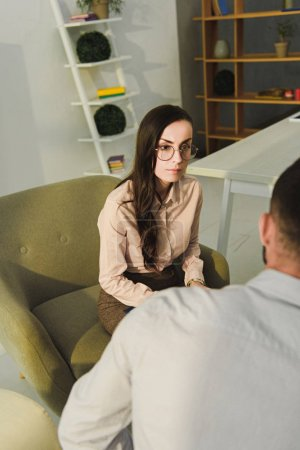 professional female psychiatrist talking with patient in office