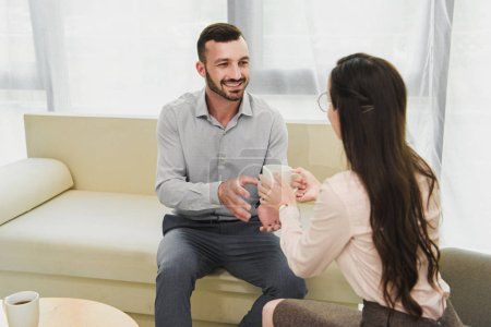 psychologist giving cup of coffee to happy patient in office