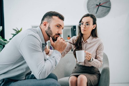 professional psychologist giving cup of tea to thoughtful patient in office