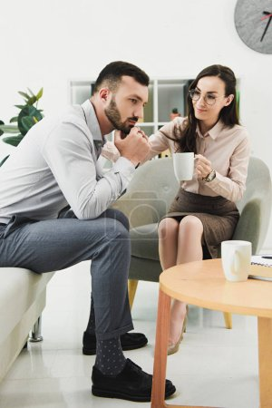 female psychologist giving cup of tea to pensive patient in office