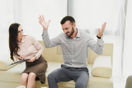 female psychiatrist with clipboard listening emotional patient gesturing in office