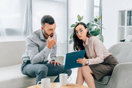 psychologist talking with male patient and showing clipboard in office
