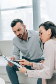 female psychiatrist talking with patient and showing clipboard in office