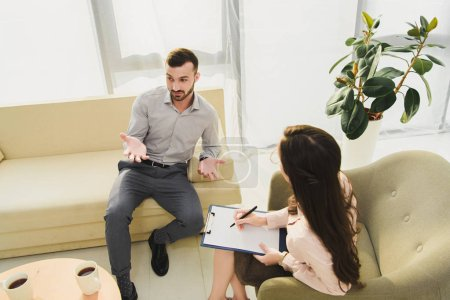 psychiatrist with clipboard having consultation with male patient in office