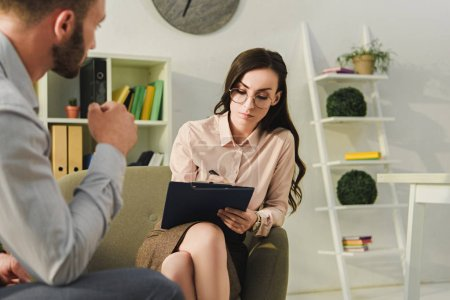 Photo for Female psychologist talking with male patient and writing diagnosis in office - Royalty Free Image