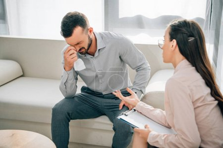 psychologist with clipboard talking to crying male patient in office