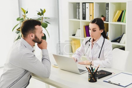client and doctor in medical office with laptop