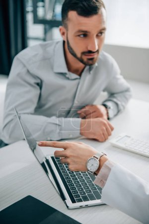 cropped view of doctor showing something on laptop screen to client in office