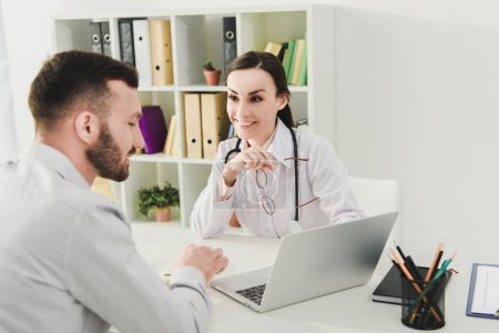smiling doctor and man discussing health insurance and looking on laptop screen in clinic