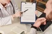 cropped view of doctor showing insurance claim form to client