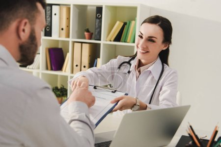 smiling doctor showing insurance claim form to client in office, life insurance concept