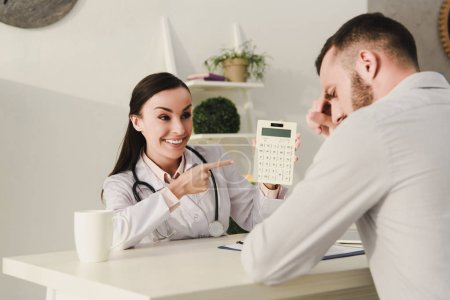 smiling client and professional doctor counting finances on calculator for life insurance in office