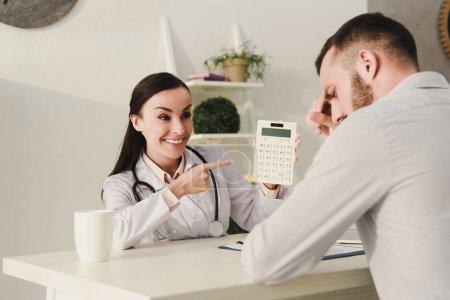 Photo pour Souriant le client et le professionnel médecin comptage finances sur calculatrice d'assurance vie au bureau - image libre de droit