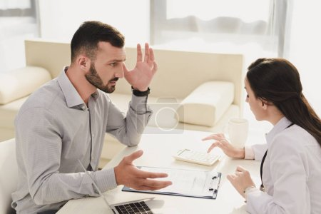 frustrated client looking at doctor counting finances on calculator, life insurance concept