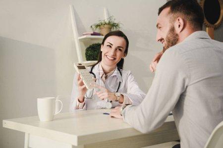 Photo pour Client souriant et médecin comptage des finances sur la calculatrice de l'assurance maladie - image libre de droit